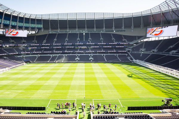 """The pitch at the Tottenham Hotspur Stadium with the SNS logo on the """"Jumbtron"""""""